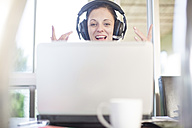 Happy woman at desk with laptop and headset - ZEF11583