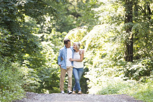 Happy senior couple walking arm in arm in the woods - HAPF01062