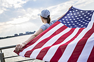 Back view of woman with basecap holding American Flag - GIOF01611