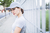 Portrait of woman wearing basecap leaning against fence - GIOF01617