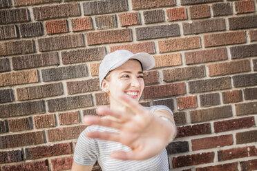 Smiling woman raising her hand - GIOF01623