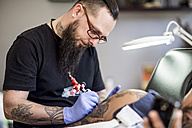 Tattoo artist tattooing an arm - ZEF11584