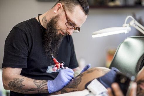 Tattoo artist tattooing an arm - ZEF11584