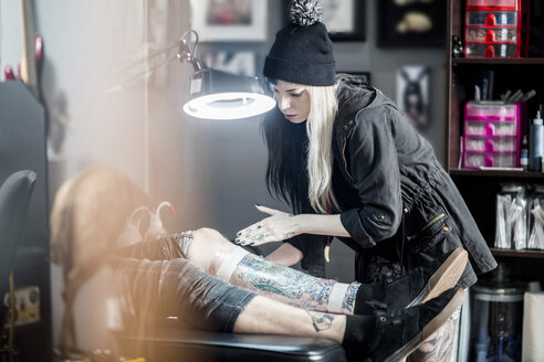Female tattoo artist applying protective wrap on finished tattoo - ZEF11599