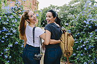 Two happy young women with camera and backpack - GEMF01227