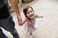 Laughing little girl holding mother's hand - VABF00836