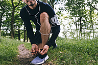 Jogger tying his shoes - BOYF00635