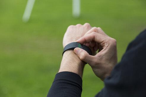 Jogger adjusting activity tracker - BOYF00638