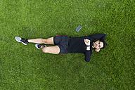 Jogger lying in grass looking on watch - BOYF00641