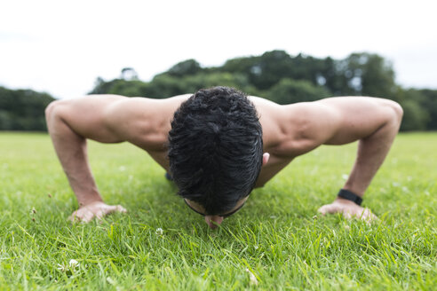Athlete doing push-ups on meadow - BOYF00653