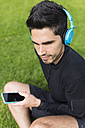 Athlete sitting in grass listening to music - BOYF00662