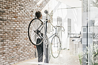 Businessman carrying bicycle in office - KNSF00440