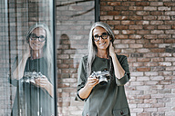 Portrait of smiling woman with long grey hair holding camera - KNSF00446