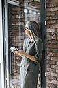 Woman with long grey hair holding camera - KNSF00449