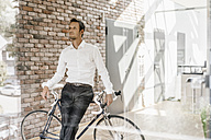Businessman with bicycle in office - KNSF00455