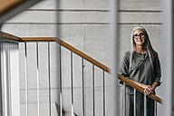 Portrait of smiling woman with long grey hair in staircase - KNSF00458