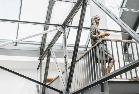 Woman with long grey hair in a loft - KNSF00470
