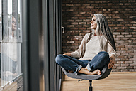 Woman with long grey hair sitting on chair at the window - KNSF00473