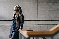 Smiling woman with long grey hair in staircase - KNSF00497