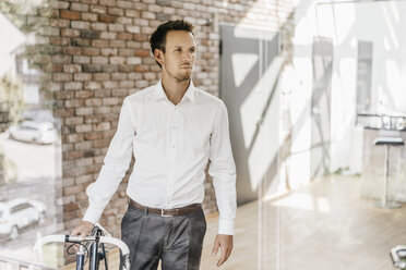 Businessman with bicycle in office - KNSF00515