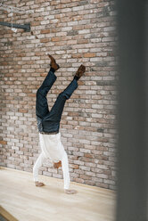 Businessman doing a handstand in front of brick wall - KNSF00521