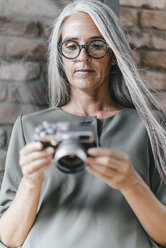 Woman with long grey hair holding camera - KNSF00524