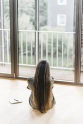 Woman sitting on the floor looking out of window - KNSF00536