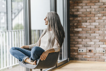 Woman with long grey hair sitting on chair at the window - KNSF00548
