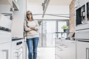 Smiling woman with long grey hair in kitchen - KNSF00554