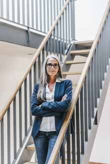 Confident businesswoman with long grey hair standing on stairs - KNSF00563