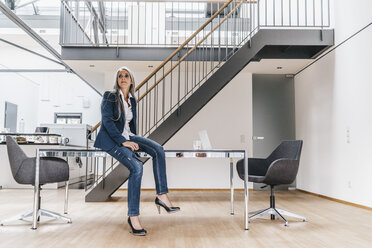 Businesswoman with long grey hair sitting on desk in office - KNSF00572