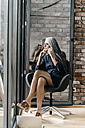 Woman with long grey hair on cell phone sitting at the window - KNSF00581