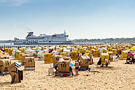 Germany, Travemuende, crowded beach with hooded beach chairs and  driving ferry in the background - FR00486