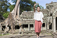 Cambodia, Angkor, Siem Reap, tourist taking selfie in front of Preah Khan temple - MADF01221