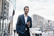 Germany, Berlin, smiling businessman with cell phone - KNSF00589