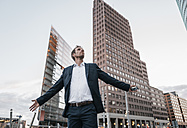 Germany, Berlin, businessman with arms outstretched standing at Potsdamer Platz in the evening - KNSF00643