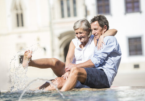 Senior couple sitting barefoot on edge of fountain splashing with water - HAPF01123