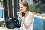 Redheaded woman drinking coffee at sidewalk cafe - TAMF00776
