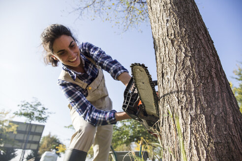 Woman on farm cuttiing tree with chain saw - ABZF01489