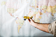 Man holding airplane in front of word map - JRFF01027