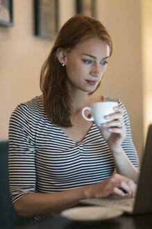 Portrait of woman sitting in a coffee shop using laptop - TAMF00785