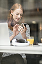Portrait of woman text messaging in a coffee shop - TAMF00791