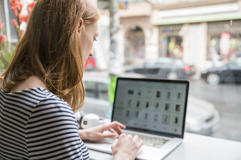 Woman using laptop in a coffee shop - TAMF00794