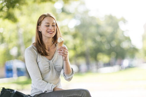 Smiling woman eating icecream - TAMF00800