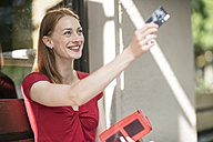 Portrait of smiling woman paying with credit card - TAMF00803