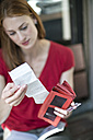 Woman checking sales slip - TAMF00806