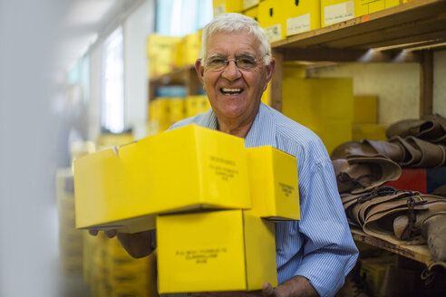 Smiling senior man in warehouse carrying shoe boxes - ZEF11617