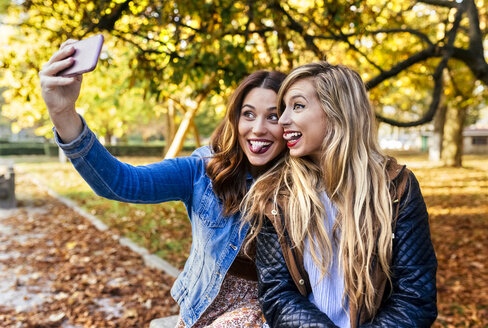 Two playful young women taking a selfie in a park in autumn - MGOF02594