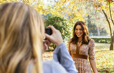 Two young women taking pictures in a park in autumn - MGOF02597