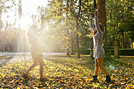 Two playful young women in a park in autumn - MGOF02600